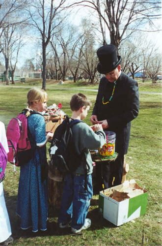 A man dressed in old attire bartering with students